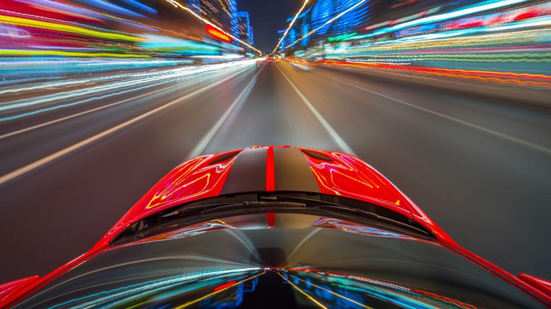 Auto rossa sportiva che corre in una strada.