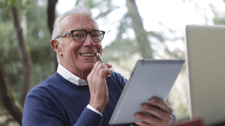Uomo anziano al tablet che legge e scrive.
