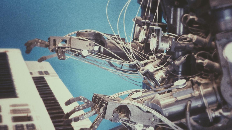 Robot al pianoforte che suona accordi.