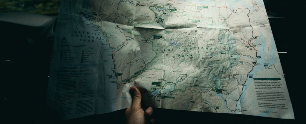 Una persona tiene in mano una cartina stradale mentre viaggia in macchina.