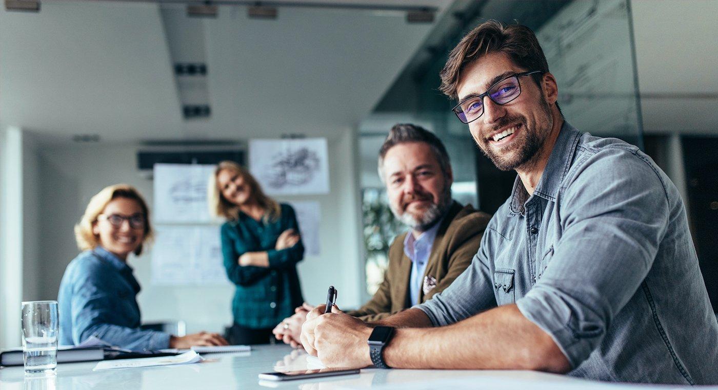 Gruppo felice di uomini d'affari durante la presentazione. I colleghi guardano la macchina fotografica e sorridono.