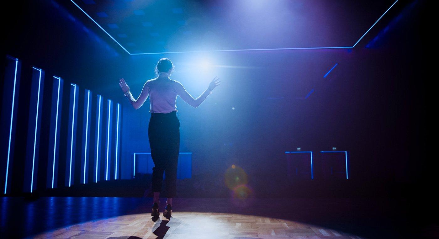 Spreaker donna sul palco, saluta il pubblico e inizia la performance.