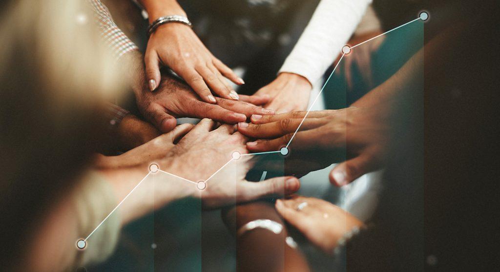 Persone che si uniscono per mano: il successo del lavoro di squadra.