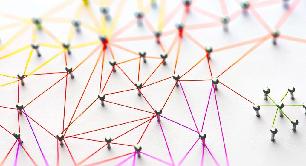 Networking, social media, SNS, internet communication abstract. Piccola rete connessa a una rete più grande. Rete di fili rossi, arancioni e gialli su sfondo bianco.
